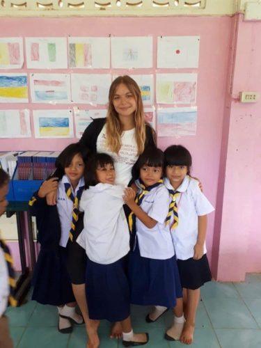 Jülide Oehlhoff mit thailändischen Kindern, die Flaggen im Englischunterricht malen
