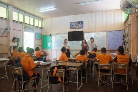Mehrere Lehrerinnen stehen vor einer Klasse Schülerinnen und Schüler in Thailand