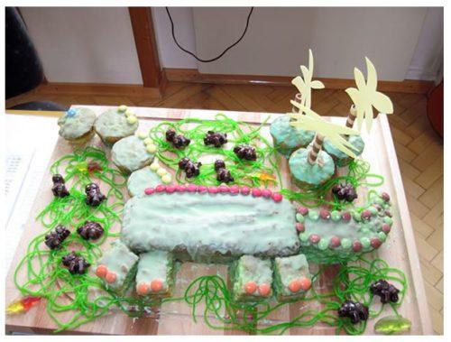 Ein selbstgebackener Kuchen mit einem Dinosaurier drauf.