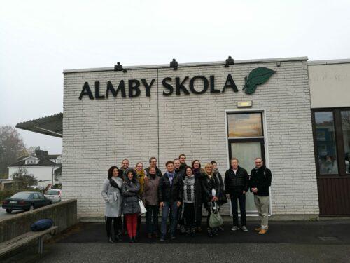 Die Projektteilnehmer/innen stehen vor der schwedischen Schule und posieren für ein Gruppenbild.