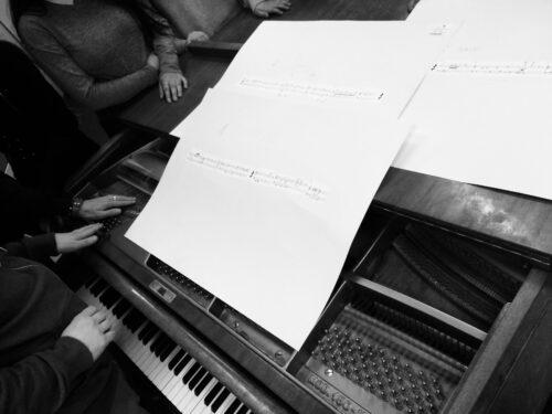 Man sieht ein Klavier oder ähnliches Instrument mit Noten auf dem Ständer. Um das Instrument sitzen Menschen, deren Gesichter man nicht sehen kann.