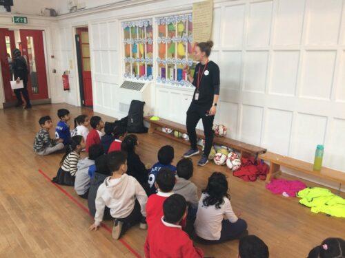 Frau Smith steht vor einer Grundschulklasse in einer Turnhalle und erklärt den Kindern Fußball