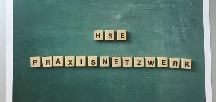 """Buchstabenwürfel bilden die Worte """"HSE"""" und """"Praxisnetzwerk"""" vor einem grünen Hintergrund."""