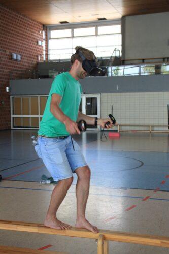 Ein junger Mann balanciert auf einem niedrigen Balken in einer SPorthalle, während er eine VR-Brille trägt.