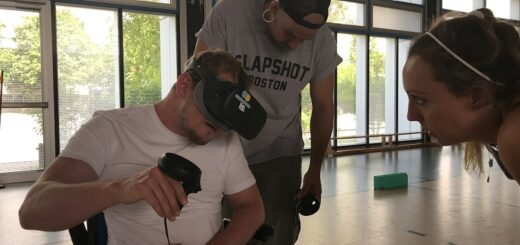 Ein junger Rollstuhlfahrer nutzt mit Anleitung zweier Personen eine VR-Brille in einer Sporthalle.