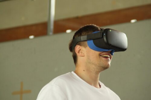 Ein junger Mann hat eine VR-Brille auf dem Kopf. Er lächelt dabei.