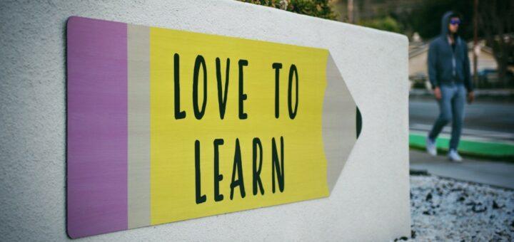 """Ein Wegweiserschild deutet nach rechts. Auf diesem Schild steht """"love to learn""""."""